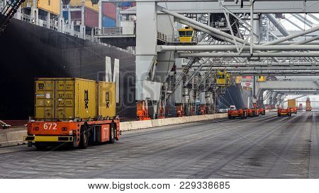 Rotterdam, Sep 6, 2013: Automated Guided Vehicles Moving Shipping Containers To And From Gantry Cran