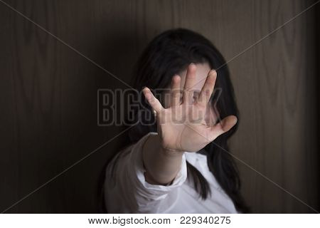 Woman With Hand Stretched As A Stop Symbol - Brunette Woman Holding Her Hand Stretched Out Toward Th