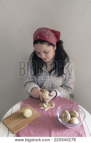 Woman Peeling Potatoes - Young Woman, Dressed Casual, Preparing A Meal With Potatoes, In Her Kitchen