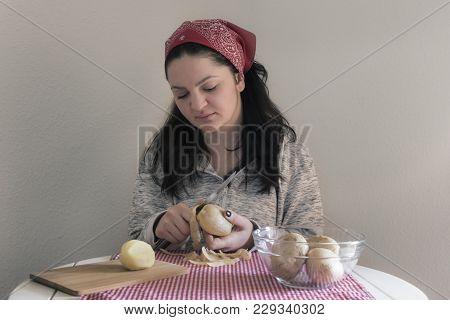 Brunette Woman Peeling Potatoes - Brunette Woman Peeling Potatoes To Prepare A Meal, On A White Tabl