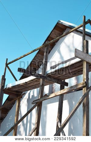 White Unfinished Wall Decoration With Window And Wooden Scaffold On Blue Sky Backround. Old House Re