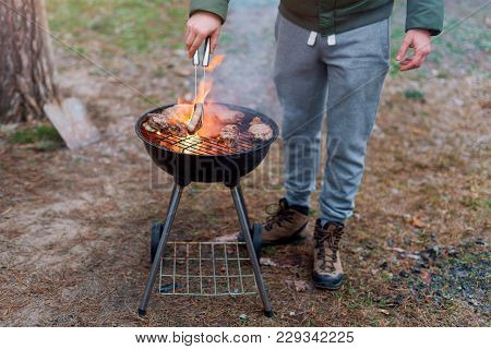 Man Cooking, Only Hands, He Is Grilling Meat Or Steak For A Dish. Delicious Grilled Meat On Grill. B