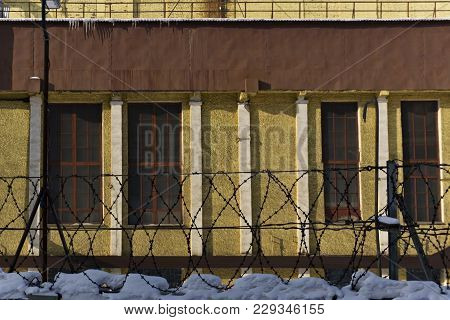 Sunlit Wall Of An Industrial Building Behind A Snow-covered Fence With Barbed Wire