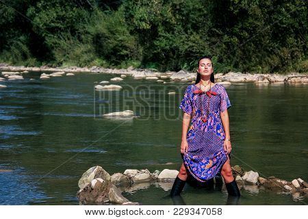 A Brunette Girl Stands Knee-deep In A Mountainous Green River In Summer.beautiful Girl Is Sitting On