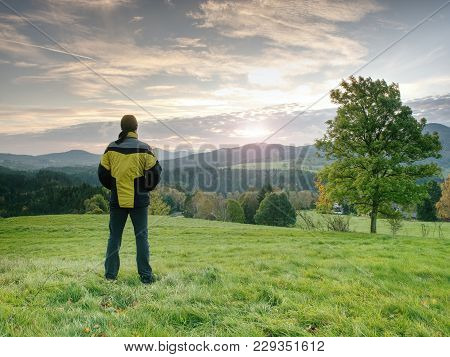 Photographer On Autumnal Meadow Is Waiting For Sunrise.  The Man Photographer With A Photocamera On
