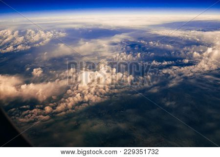 View From The Window Of The Aircraft On The Clouds And The Ground From A Height Of The Stratosphere