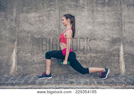 Pretty Young Slim Trainer Is Stretching Her Legs By Doing Exercise, Using Dumb Bells. She Is Trainin
