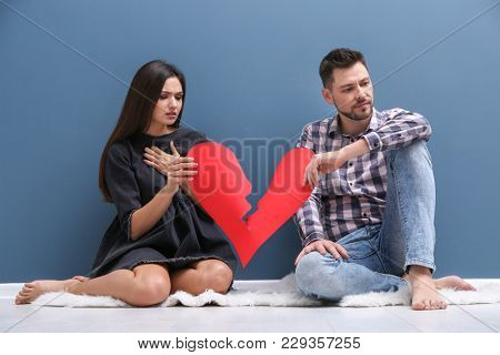 Young couple tearing paper heart in half near color wall. Relationship problems