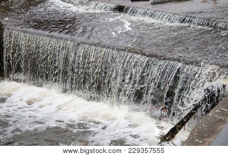 The Bubbling Waters Of The Small Waterfall On The Canal