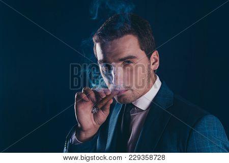 Close Up Portrait Of Attractive, Elegant, Stylish, Stunning Man Smoking Cigar Over Dark Blue Backgro