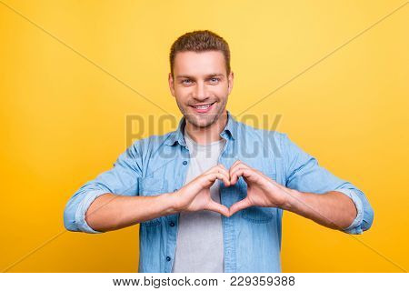 Portrait Of  Smiling, Stunning Man With Stubble Showing Heart Figure With Fingers Over Yellow Backgr