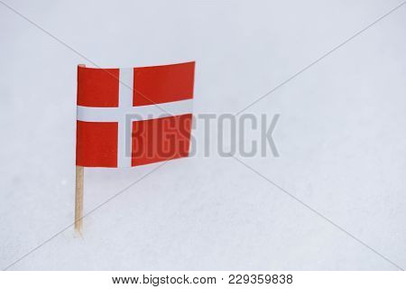 Danish flag made from paper with brown toothpick on white snow background poster