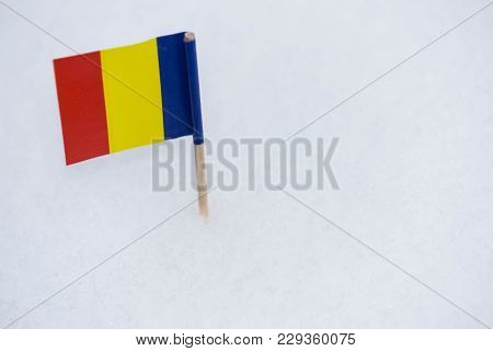 Romanian Flag Made From Paper With Brown Toothpick On White Snow Background