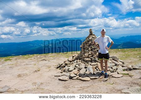 Summer Hiking In The Mountains. Young Tourist Man In A Cap With Hands Up On The Top Of The Mountains