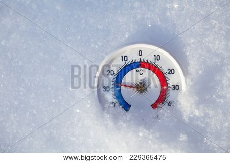 Thermometer with celsius scale placed in a fresh snow showing sub-zero temperature minus 26 degree - extreme cold winter weather concept