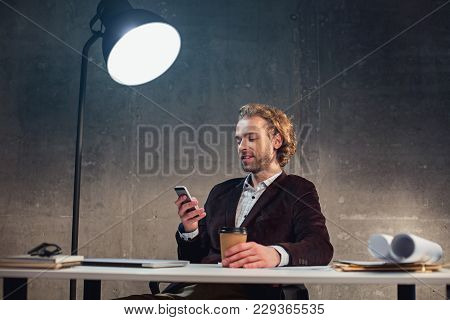 Portrait Of Satisfied Bearded Male Typing In Mobile While Tasting Mug Of Beverage. He Sitting At Des