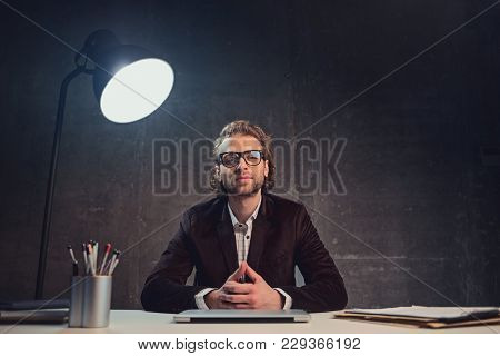 Portrait Of Smiling Unshaven Clever Businessman Working At Table. Labor Concept