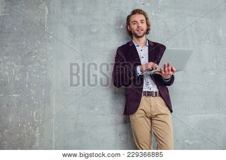 Portrait Of Beaming Unshaven Businessman Typing In Laptop. Employer Having Job With Gadget Concept.