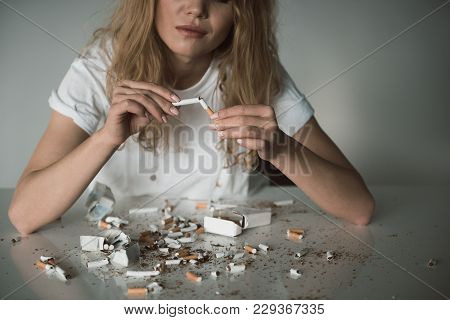 Young Female Holding Ciggy And Smiling, Shredded Cigarettes Are Lying On Table. Isolated On Backgrou
