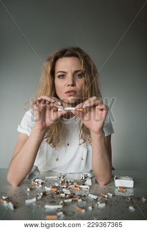 Portrait Of Serene Female Holding Cigarette And Looking At Camera, Smashed Cigars Are Lying On Table