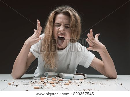Portrait Of Impetuous Woman Sitting At Table With Smashed Cigarettes, She Is Holding Hands Up And Ma