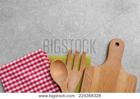 Wooden cooking utensils and napkins on gray background, top view