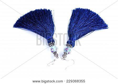 Blue Handmade Tassel Earrings On A White Background.