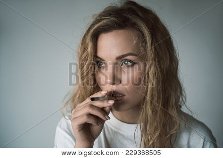 Portrait Of Thoughtful Woman Looking Aside While Holding Cigarette Stubbed With Prickles. Isolated O