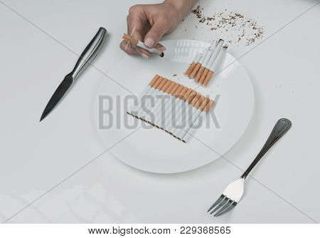 Close Up Of Female Hand Picking Up From The Plate Cigarette Pierced With Needles