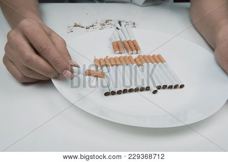 Life Threatening Concept. Close Up Of Woman Arm Keeping Spiny Coffin Nail Over Plate Full Of Cigaret