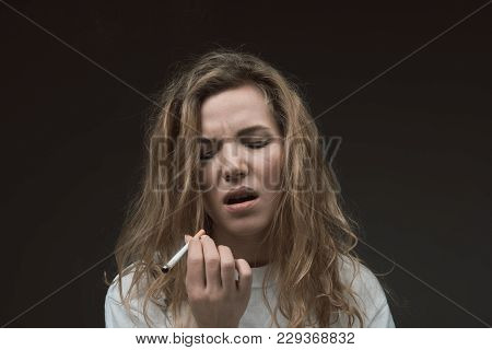 Portrait Of Peaceful Female Person Standing With Eyes Closed From Pleasure. She Is Holding Cigarette