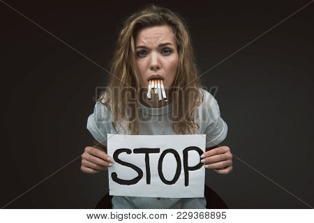 Waist Up Portrait Of Serious Woman With Stop Word Written On Poster. She Is Having Vomiting Reflex F