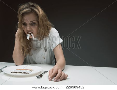 Portrait Of Gloomy Woman With Mouth Full Of Rollups Relaxing At The Desk. Nicotine Dish Standing On