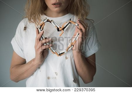 Peaceful Woman Holding Heart Made Of Cigarettes In Front Of Chest. Copy Space In Right Side. Isolate
