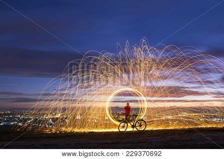 Firework Showers Of Hot Glowing Sparks From Spinning Steel Wool Over Night City Background. Art Show