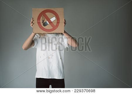 Female Person Covering Her Face With Poster Depicting Crossed Out Cigarette. Copy Space In Right Sid