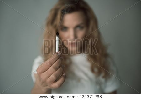Portrait Of Unhappy Woman Demonstrating Burning Ciggy. Focus On Coffin Nail. Isolated On Background