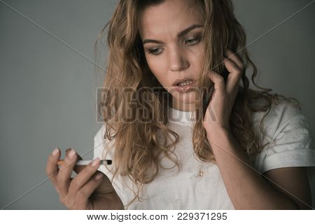 Portrait Of Nervous Young Girl Looking At Cigarette In Her Hand With Discontent. Isolated On Backgro