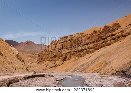 Lonely Car Riding Through Curly Road In Canyon Along The River On Himalaya Highlands. Scenic Landsca