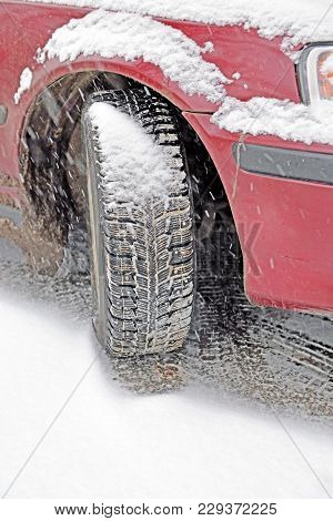 Winter Automobile Tire On  Wheel Of  Red Car Which Stopped Recently. Heavy Snowfall  Fast Covers Up