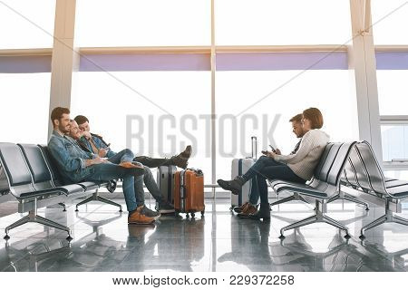 Full Length Happy Friends Waiting For Plane In Airport. They Talking Together And Typing In Phones.
