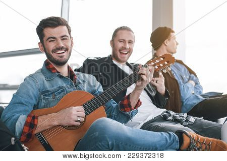 Laughing Friends Situating In Room. Outgoing Male Performing Melody With Musical Instrument. Friends