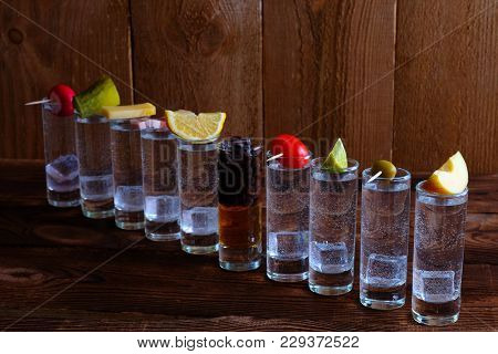 Shots Of Alcohol On Wooden Background. Ten Shots Of Alcohol On A Wooden Table. On Each Shot, On Top