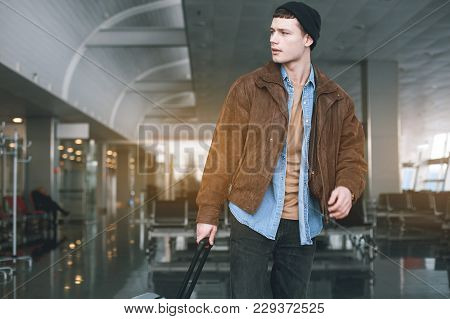 Portrait Of Serene Male Keeping Lugagge While Going In Hall. Adventure Concept