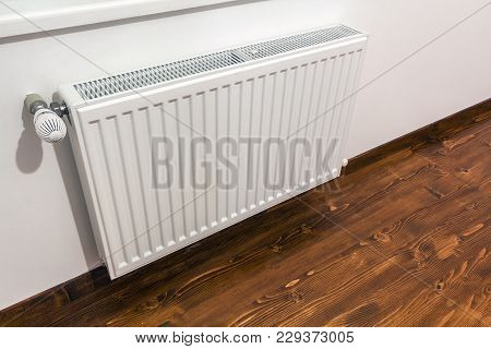 A White Heating Radiator On The Interior Wall