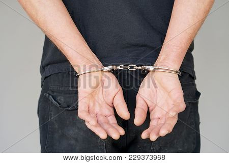Close-up. Arrested Man Handcuffed Hands At The Back. Prisoner Or Arrested Terrorist, Close-up Of Han