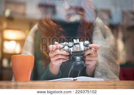 Low Angle Focus Close Up Of Female Hands Holding Camera. Girl Is Looking At Screen With Interest Whi