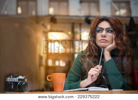 Portrait Of Pensive Young Lady Creating Poem In Diary. She Is Holding Pencil While Wearing Headphone