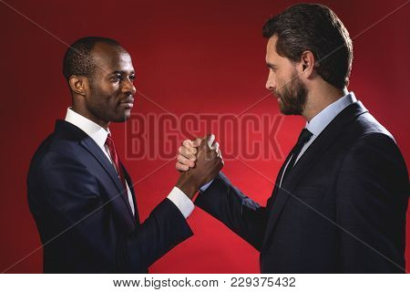 Partnership Concept. Side View Profile Of Two Pleasant Skilled Businessmen Are Standing And Having S