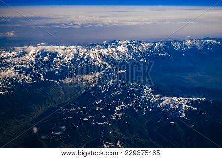 Mountains With Snowy Peaks And Sky With Blue Clouds From The Stratosphere